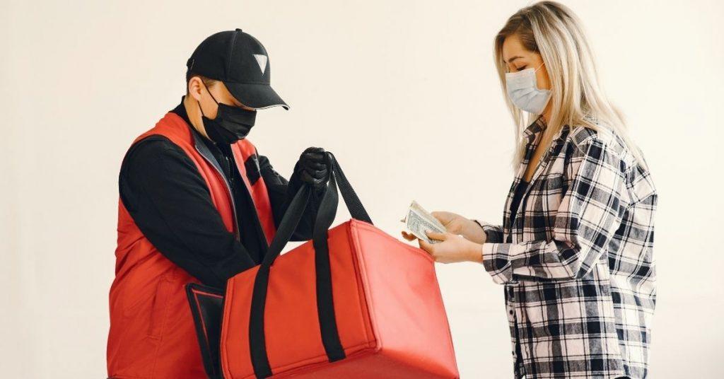 Un livreur donne son colis à une cliente qui a réservé via WhatsApp