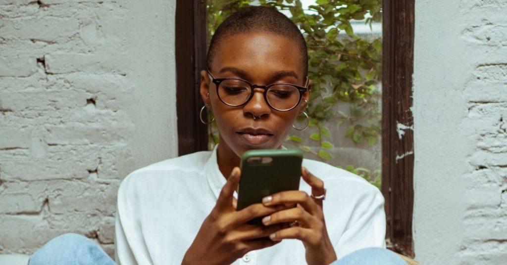 Jeune femme en train de communiquer avec une entreprise sur WhatsApp